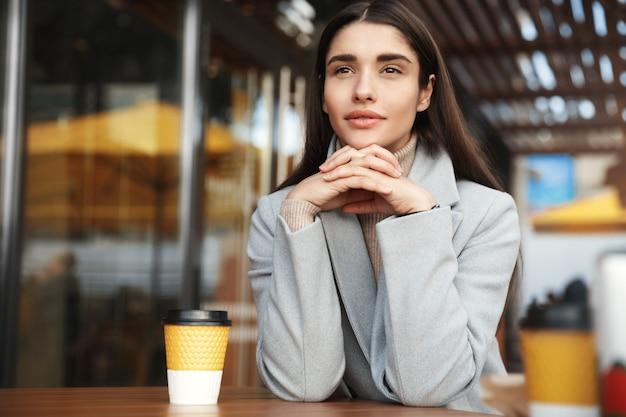 Jovem mulher sonhadora tomando café em um café e olhando para a rua.