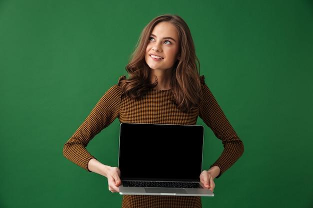 Jovem mulher sonhando segurando um laptop mostrando a tela