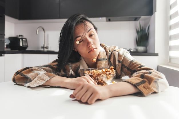 Jovem mulher sonolenta acordando na cozinha com pipoca presa no rosto