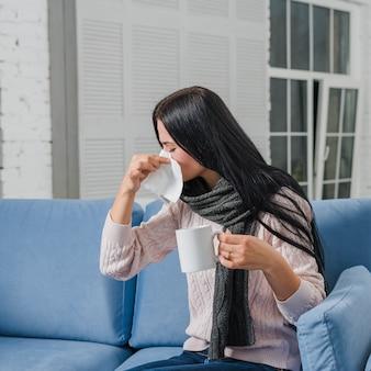 Jovem mulher soprando o nariz com lenço de papel, segurando a caneca de café na mão