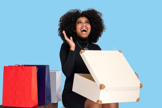 Jovem mulher sorrendo feliz ao abrir a caixa de presentes, sentada e ao lado de suas várias sacolas de compras