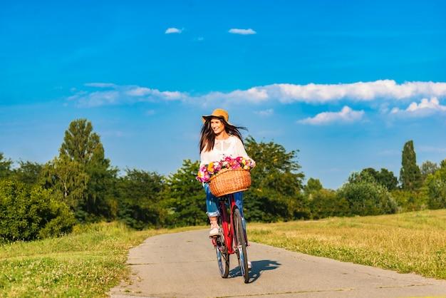 Jovem mulher sorridente anda de bicicleta em counrtyside