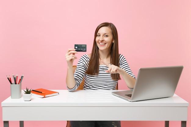Jovem mulher sorridente apontando o dedo indicador na cadeira do cartão de crédito, trabalhar na mesa branca com o laptop do pc