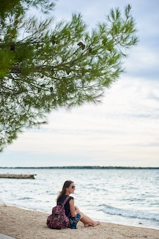 Jovem mulher sorridente atraente com mochila colorida, sentado sozinho na praia do oceano na água azul brilhante e céu claro