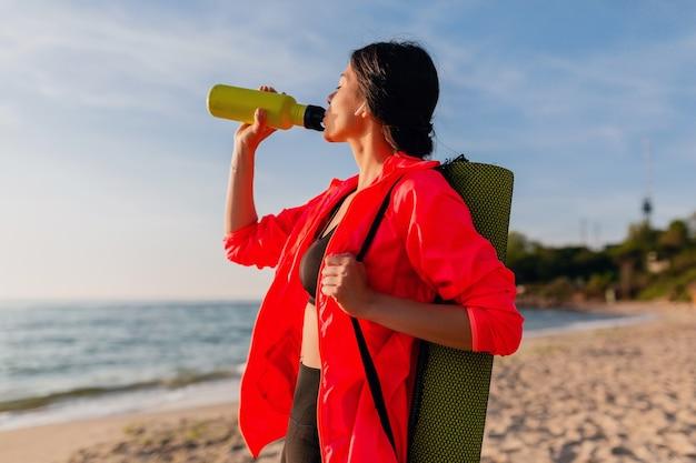 Jovem mulher sorridente atraente praticando esportes no nascer do sol da manhã na praia do mar segurando um tapete de ioga e uma garrafa de água, estilo de vida saudável, ouvindo música em fones de ouvido e vestindo uma jaqueta corta-vento rosa