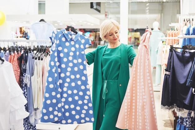 Jovem mulher sorridente bonita faz escolha ao fazer compras em uma loja