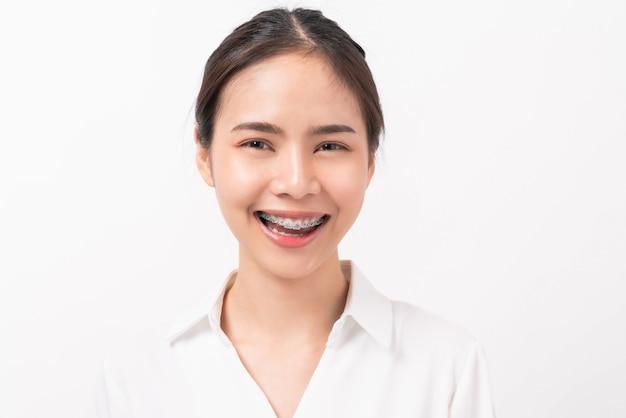 Jovem mulher sorridente com aparelho nos dentes