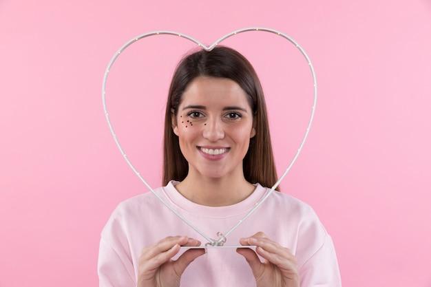 Jovem mulher sorridente com brilhos no rosto segurando coração decorativa