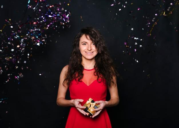 Jovem mulher sorridente com caixa de presente entre confetes jogando