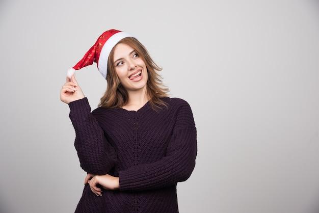 Jovem mulher sorridente com chapéu de papai noel em pé e posando.