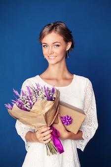 Jovem mulher sorridente com flores e caixa de presente