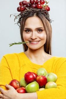 Jovem mulher sorridente com frutas. uma linda morena com um suéter amarelo com uvas roxas na cabeça