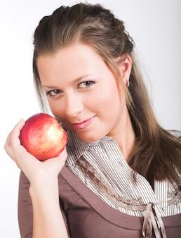Jovem mulher sorridente com maçã vermelha.