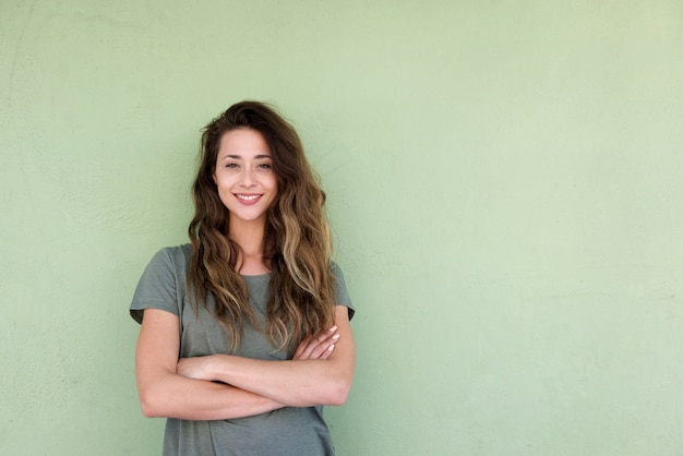 Jovem mulher sorridente com os braços cruzados contra o fundo verde