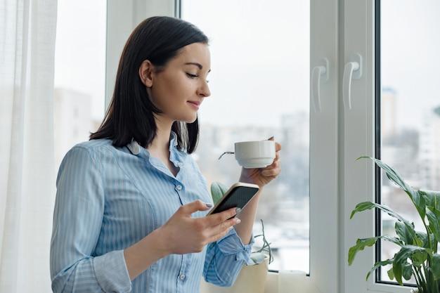 Jovem mulher sorridente com uma xícara de café, lendo o texto no smartphone