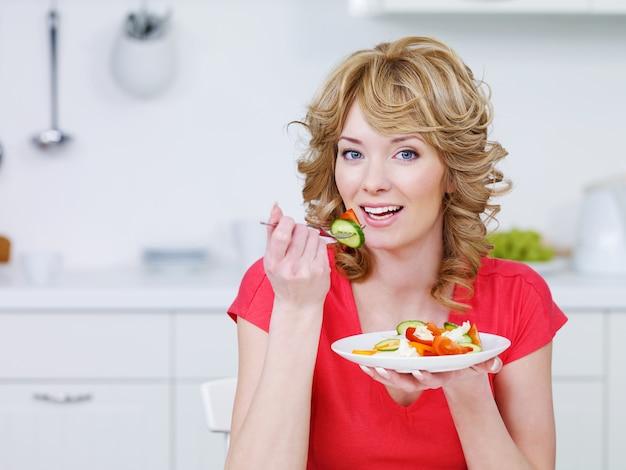 Jovem mulher sorridente comendo salada na cozinha - dentro de casa