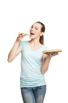 Jovem mulher sorridente comendo um pedaço de pizza, isolado no branco