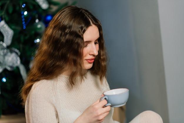 Jovem mulher sorridente de suéter, férias de inverno no interior de casa decorada com árvore de natal.