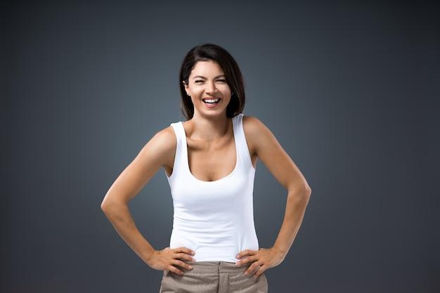 Jovem mulher sorridente e atraente em pé com as mãos na cintura