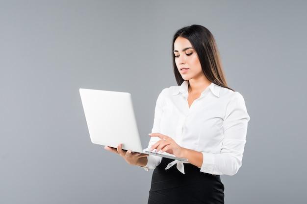 Jovem mulher sorridente e feliz segurando um laptop e enviando e-mail isolado em cinza