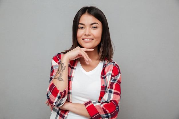 Jovem mulher sorridente em cima de parede cinza