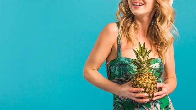 Jovem, mulher sorridente, em, flowered, vestido, segurando, abacaxi