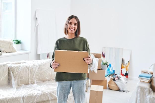 Jovem mulher sorridente em trajes casuais segurando uma caixa de papelão enquanto está de pé na sala de estar de um apartamento ou casa nova