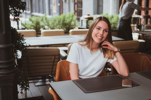Jovem mulher sorridente em um café de rua