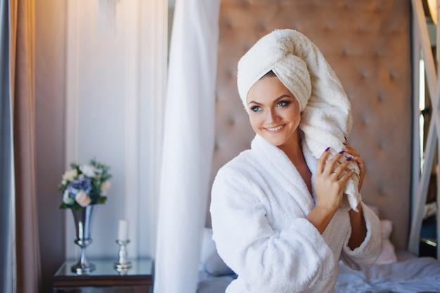 Jovem mulher sorridente em um roupão de banho, interior do hotel