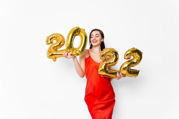 Jovem mulher sorridente em um vestido de cocktail vermelho com maquiagem brilhante, comemorando o ano novo e segurando golde.