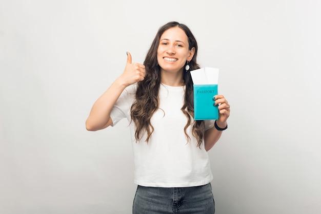 Jovem mulher sorridente está segurando o passaporte e as passagens aéreas.