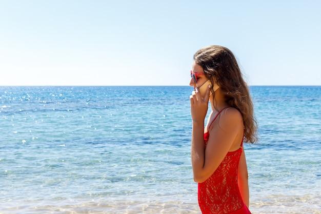 Jovem mulher sorridente, falando por telefone em uma praia