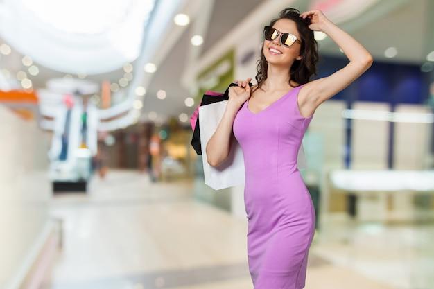 Jovem mulher sorridente feliz com sacos de compras