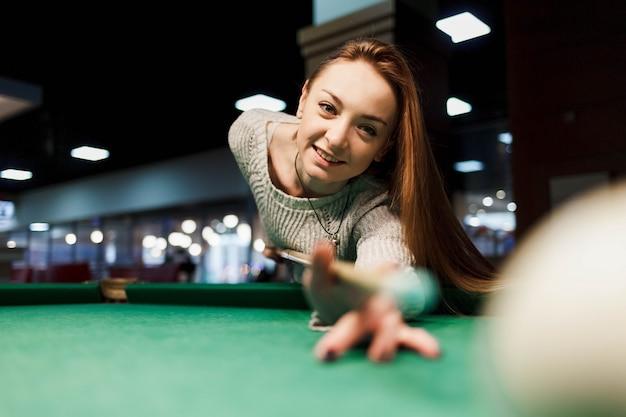 Jovem mulher sorridente joga bilhar no clube de bilhar