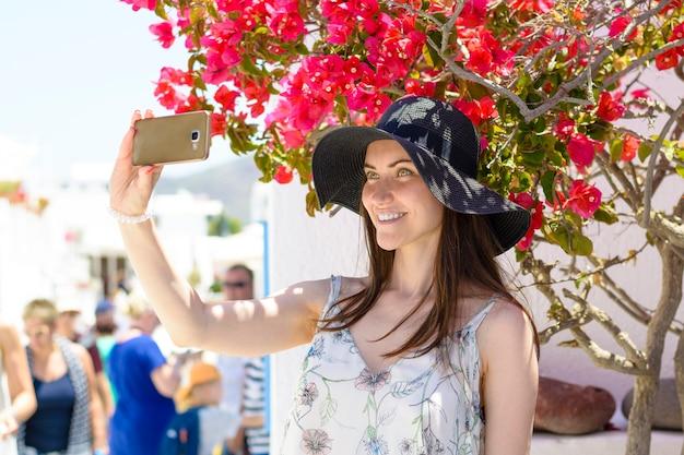 Jovem mulher sorridente no chapéu tomando uma selfie de férias