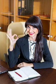 Jovem mulher sorridente no escritório mostrando o símbolo bem