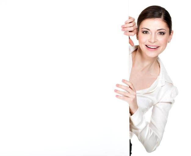 Jovem mulher sorridente olhando de uma faixa branca em branco - no espaço em branco