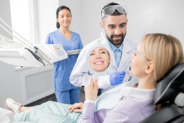 Jovem mulher sorridente, olhando no espelho após procedimento de clareamento profissional, enquanto está sentada na poltrona do consultório dentista