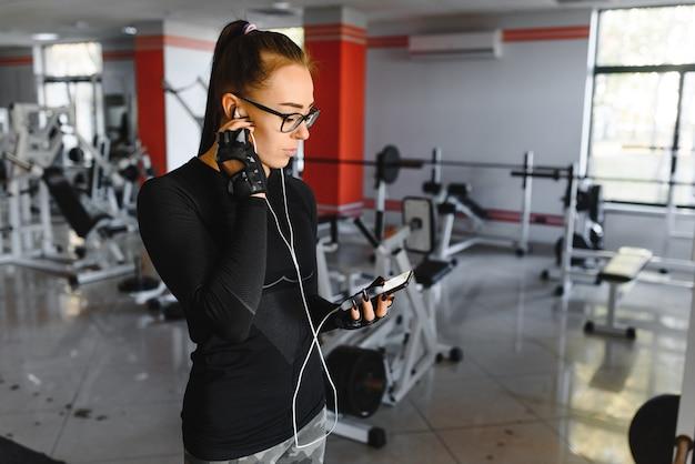 Jovem mulher sorridente, ouvindo música em smartphone no ginásio.