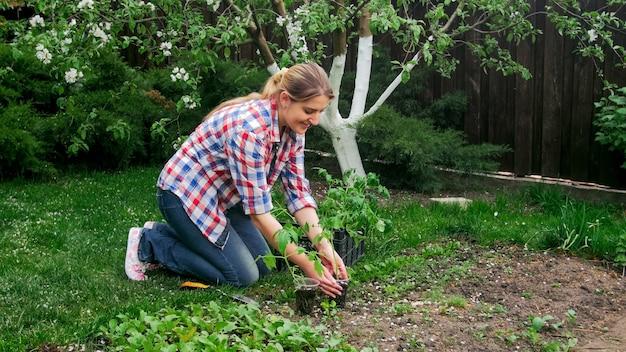 Jovem mulher sorridente, plantando mudas de vegetais no jardim.