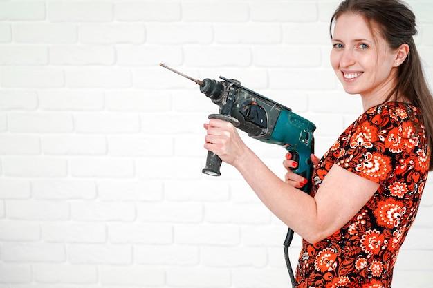 Jovem mulher sorridente posando com martelo