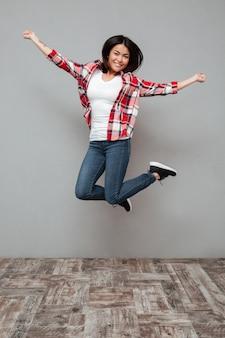 Jovem mulher sorridente pulando parede cinza.