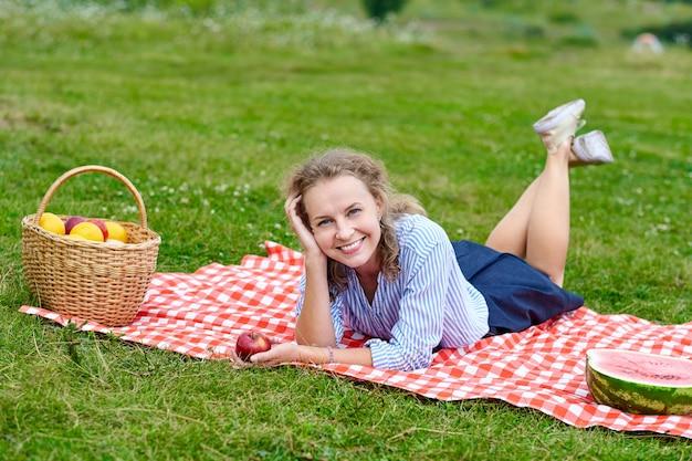 Jovem mulher sorridente, relaxante ao ar livre e fazendo um piquenique, ela está deitada sobre um cobertor de glóbulos vermelhos na grama em um prado.