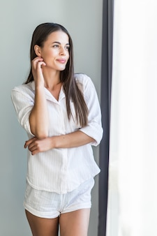 Jovem mulher sorridente relaxante em casa aconchegante, sentindo-se feliz, descansando de manhã, olhando pela janela