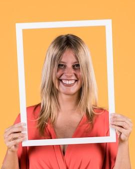 Jovem mulher sorridente segurando a moldura de foto de borda branca na frente de seu rosto