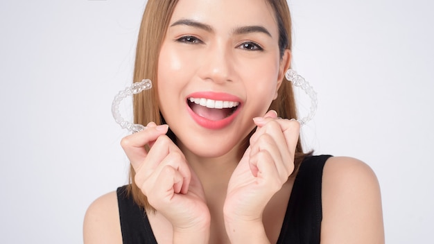 Jovem mulher sorridente segurando aparelho invisalign em estúdio, conceito de saúde odontológica e ortodôntica