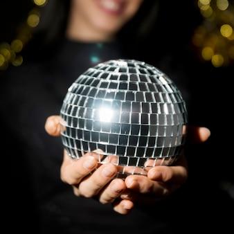 Jovem mulher sorridente segurando bola de discoteca