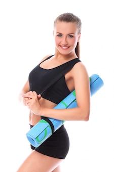 Jovem mulher sorridente segurando esteira para fitness
