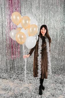 Jovem mulher sorridente segurando muitos balões perto ouropel
