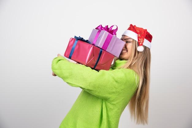 Jovem mulher sorridente segurando nas mãos presentes de natal festivos.